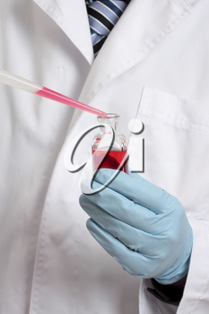 Scientist, chemist, pharmacist or laboratory technician adding a pipetted sample to a laboratory bottle. Focus to hand, pipet and bottle
