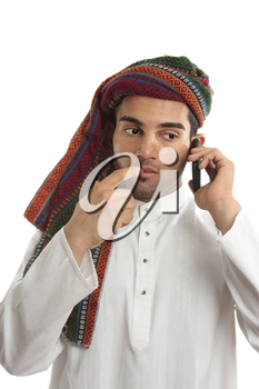 Pondering arab ethnic middle eastern businessman dressed in traditional clothing.   He is using a mobile cellphone. White background.