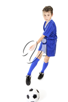 Child kicking or manoeuvring a soccer ball.  Motion to ball and kicking foot.