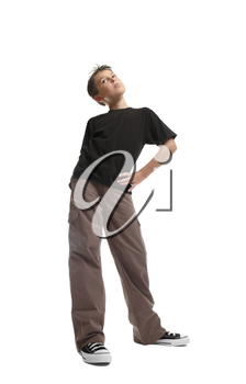 Standing boy in a plain  black t-shirt and cargos.  He is looking sideways. viewpoint from ground level.