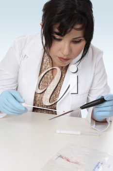Forensic investigator takes a sample from a knife for further analysis.
