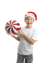 An excited ecstatic boy holding a big Christmas bauble ball decoration.  Red and white with sparkling glitter and a silver thread
