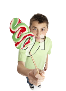 Boy holds our a Christmas tree lollipop on a stick - above view with focus to candy. Shadow under feet.