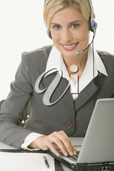 Portrait of friendly smiling customer support operator sitting at the table in a working environment