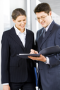 Portrait of two business people standing in the office looking into folder with business plan with smiles