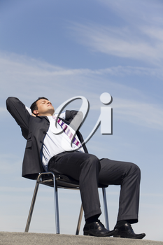 Portrait of sitting businessman with his eyes closed and hands behind head outside at summertime