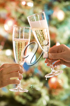 Image of two glasses of champagne in the hand on the background of christmas- tree