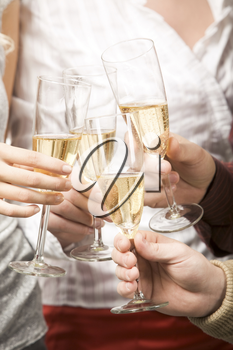 Close-up of friends hands holding glasses with champagne and making cheers