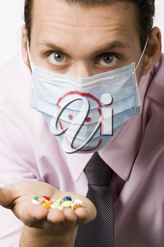 Photo of masked man holding pills and looking at camera