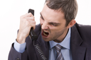 Image of aggressive boss yelling into telephone receiver over white background
