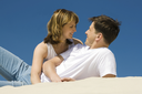Image of amorous couple lying on sandy beach and looking at each other