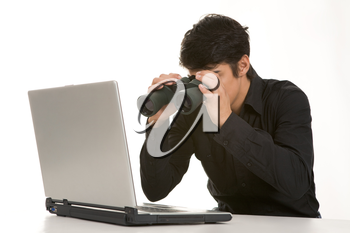Portrait of businessman holding binoculars sitting at the table with laptop on it