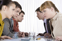 Photo of two rows of business people looking at each other with tension