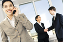 Portrait of happy woman calling on the phone on the background of business people�s handshake