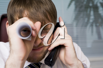 Close-up of playful man with paper roll by his eye while speaking on the phone