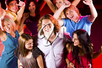 Portrait of happy guy embracing two smart girls in night club at party with their friends behind