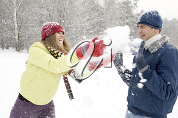 Portrait of happy couple having a fun in winter forest