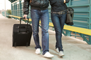 Legs of couple walking down train station with their baggage