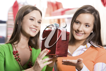 Portrait of two girls choosing gifts before Christmas in the mall