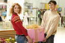 Cheerful couple carrying big box with presents for all family in supermarket