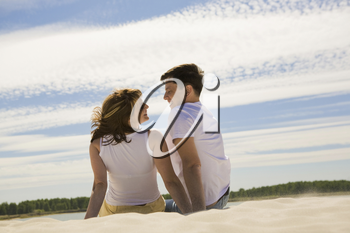 Rear view of relaxing couple sitting on sandy beach and smiling at each other