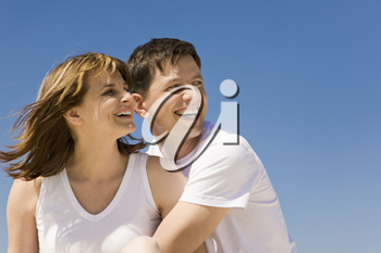 Portrait of cheerful couple looking aside against blue sky