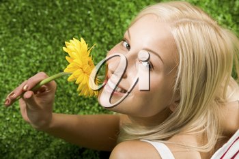 Close-up of cheerful young female with yellow beautiful flower in hands looking at camera