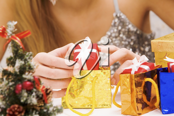 Close-up of female putting small giftbox into golden package