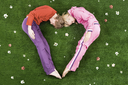 Heart formed by sleeping couple lying on green meadow