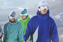 Portrait of handsome snowboarder in googles on background of his friends