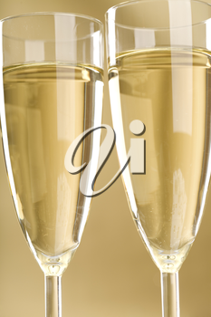 Close-up of two flutes of champagne over golden background