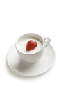 Image of red ripe strawberry heart inside cup of milk over white background