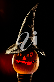 Vertical image of Halloween grinning pumpkin with hat and spiders