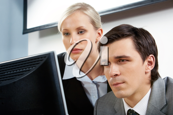 Portrait of two colleagues looking attentively at monitor over white background