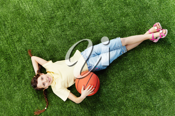 Image of happy girl lying on the grass with ball and looking at camera