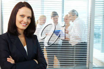 Portrait of pretty female looking at camera with smile in office