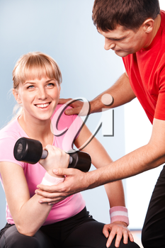 Photo of active girl lifting dumbbell in the sports club with her instructor near by