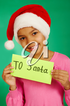 Portrait of happy girl in Santa cap holding envelope with note �To Santa�