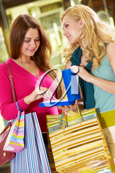 A girl with bags showing new jewelry to her friend