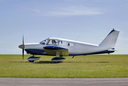 Light aircraft taxiing on a grass runway about to take off.