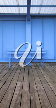 Vertical panoramic image of an empty blue bench on wooden decking