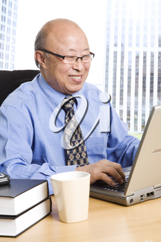 A senior asian businessman working in the office