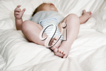 sleeping baby on a white blanket with feet