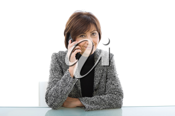 Senior businesswoman sitting at office desk talking on mobile phone, isolated on white background.