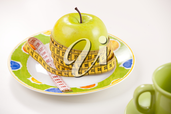 Diet concept with a green apple and a measure tape on plate.