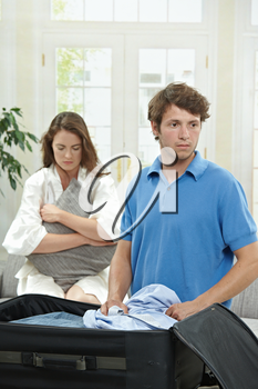 Unhappy couple breaking. Man packing his clothes into suitcase, sad woman hugging pillow in the background. Selective focus on man.