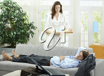 Tired businessman resting on couch at home in the morning, his wife brining breakfast on tray.