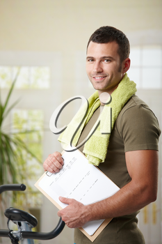 Man wearing sportswear standing in living room at home, holding training plan.
