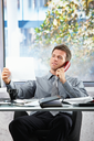 Smiling professional businessman on landline call looking at paper held in hand sitting at office desk.
