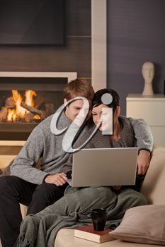 Young couple hugging on sofa at home in winter, using laptop computer, smiling.